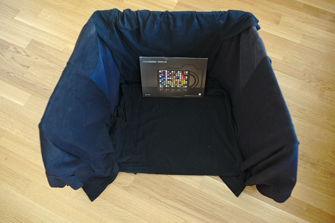 A cardboard box coated with black t-shirts